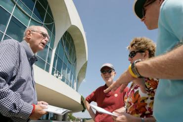 A docent gives a tour of Monona Terrace to guests standing on the lakeshore bike path