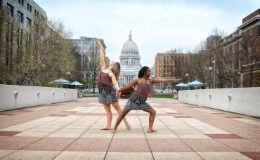 Two dancers from Madison Contemporary Dance pose in the foreground of Monona Terrace with overlapping hands and legs, the state capitol shows in the background