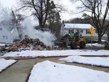 Loader from Streets Division assisting in moving recyclables so firefighters can put out the flames
