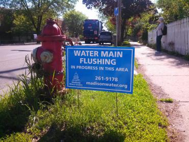 "A blue sign in a terrace reads: ""Water main flushing in progress in this area. 261-9178 madisonwater.org"""