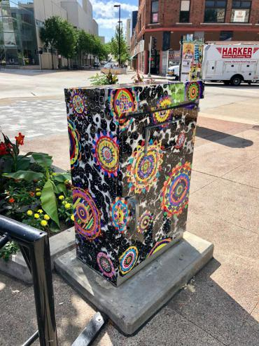 Image of utility box wrapped with artwork created by Michael Velliquette for the signal box at West Johnson and State Street