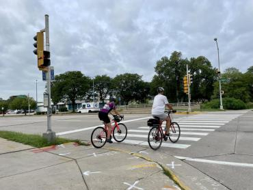 Image of 2 bicycle riders crossing at the Park Street intersection in crosswalk.