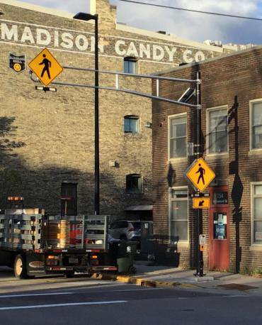 A picture of the accessible pedestrian crossing outside the Wisconsin Council for the Blind.  A brick building with a red door, in from of a 4 story brick building with a ghost sign for Madison Candy Co. on it.