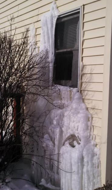 Water seeps through the siding of a vacant home with burst pipes on Madison's east side