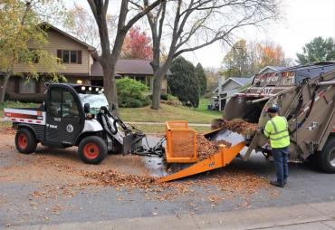 A toolcat is pushing a pile of leaves into a truck. This is the second of the three step process of collecting leaves. First is pulling from the, second is pushing into the truck, and third is street sweeping the leftover debris.
