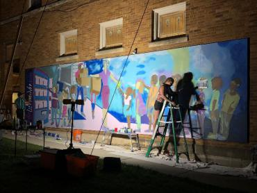 Simone Lawrence Painting Mural on Monroe Street at night with bright lights illuminating wall