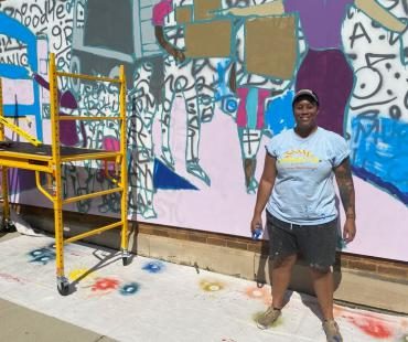 This is a photo of Simone Lawrence standing in front of her in progress mural on Monroe Street