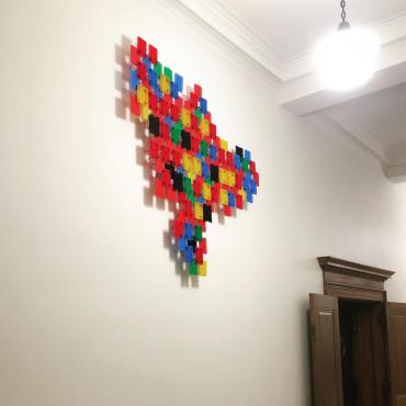 Image of About the Future (Dreaming) by Victor Castro (TetraPAKMAN), a bright sculptural assemblage created out of industrial zip ties and the plastic shipping material that lab tubes  come in. The pieces are installed high up on the hallway walls of the 2nd floor of the Madison Municipal Building