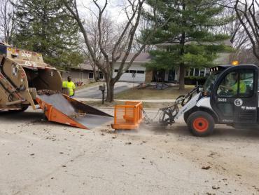Yard waste crews pushing yard waste onto pan truck