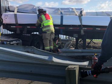 Firefighters cutting away guard rail