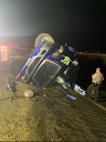 Semi rolled over with extrication equipment nearby