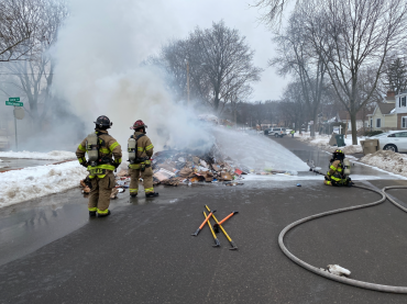 Firefighters spraying foam on pile of recyclables