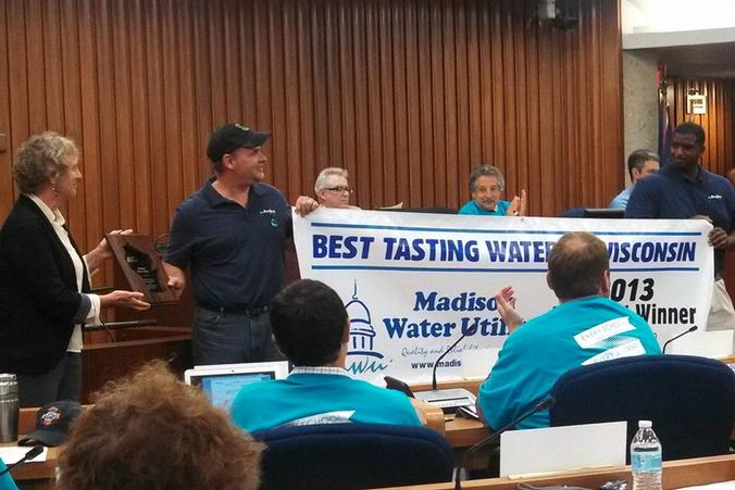 Two Madison Water Utility employees hold banner recognizing Madison's Best Tasting Water win