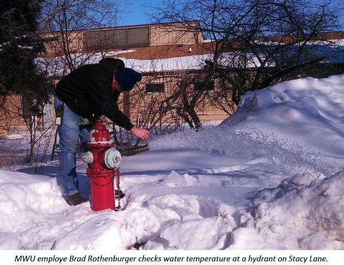 Hydrant inspector takes temperature of water running from a hydrant