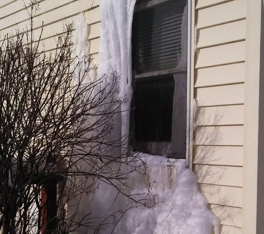 Ice dam forms where water has been seeping out of window